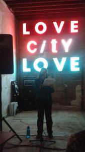 Reading about a neon sign in front of a neon sign. Photo by Waverly Fitzgerald.